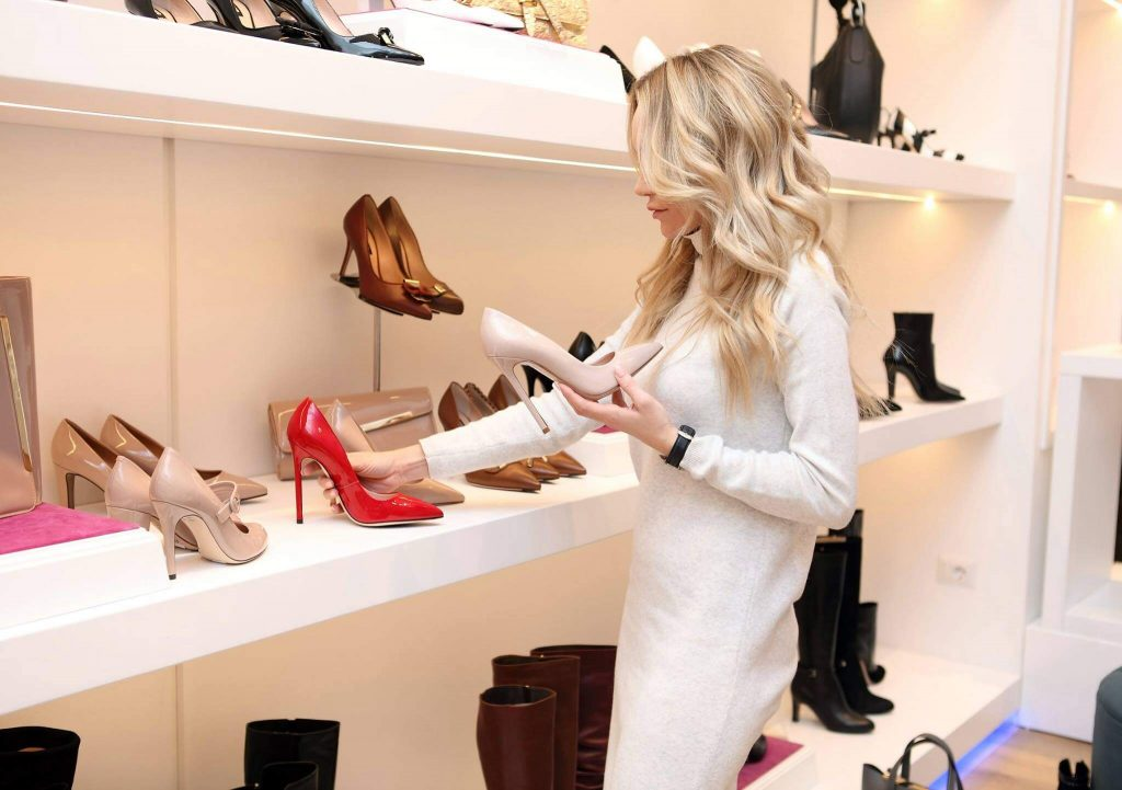 White woman with blonde hair choosing shoes